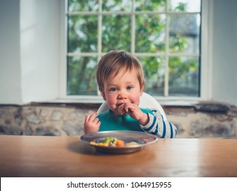 A cute little boy is sitting at the table and is eating his dinner
