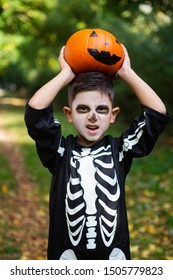 cute little boy in a skeleton in a skeleton holds a pumpkin and scares, children party halloween in the park, traditional autumn holiday