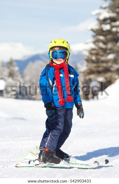 Cute little boy, skiing happily in Austrian ski resort in the mountains, wintertime