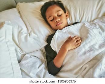 Cute little boy sleeping in bed. Low light image. Top view