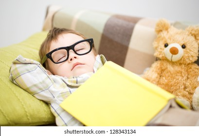 Cute little boy is sleeping in front of his teddy bears wearing glasses and put off a big book
