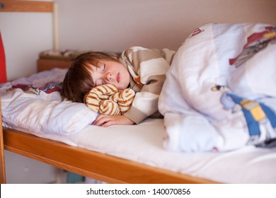 Cute little boy sleeping on bunk bed at hole