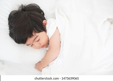 Cute little boy sleeping on the white mattress, fresh and cozy bedding sheets. Bedtime for kids.