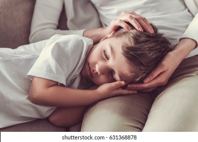 Cute little boy is sleeping on mom's knees at home