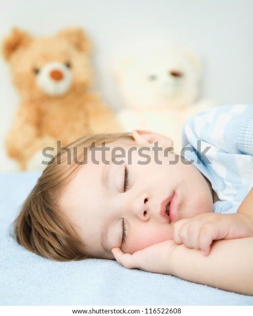 Cute little boy is sleeping on a white pillow