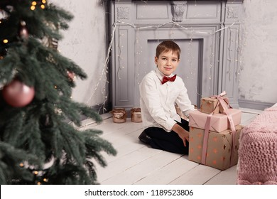 Cute little boy in a smart dress with a Christmas gift box near the New Year tree. Winter holiday.