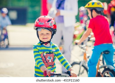 Cute Little Boy Is Is Smiling Around Bunch of Kids Riding Bikes