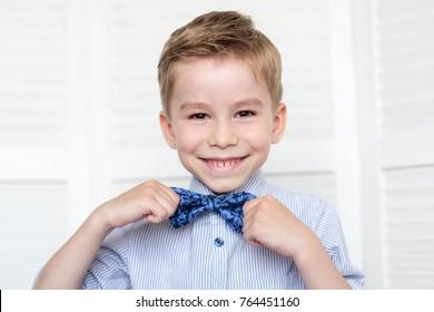 青いシャツを着て微笑むかわいい小さな男の子、両手に青い蝶ネクタイを持つ幸せな赤ちゃん。