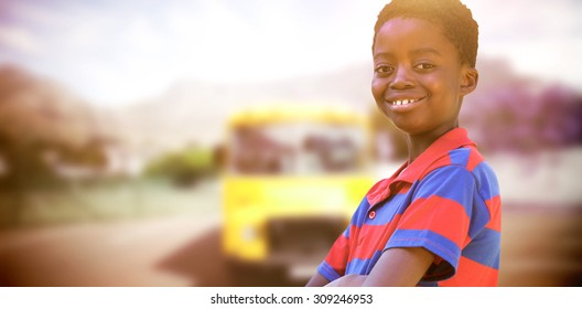Cute little boy smiling at camera against yellow school bus waiting for pupils