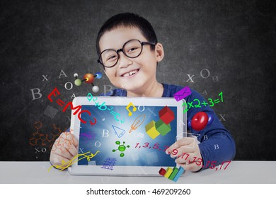 Cute little boy smiling at the camera while showing a digital tablet with formula of science, math, and physics on the screen
