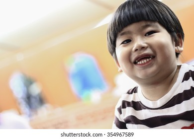 Cute Little boy smiling open wide mouth show his toothless on  A chair Sitting in the barber shop. in-Thailand.
