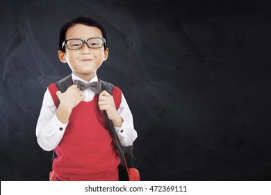 Cute little boy standing in front of the blackboard while wearing uniform and carry bag