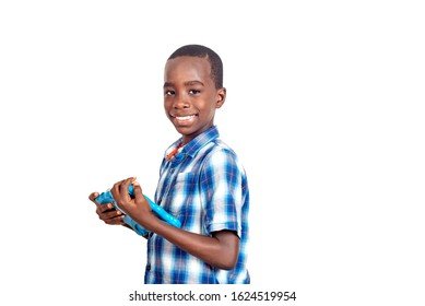 cute little boy standing inside holding a digital tablet and smiling at the camera.