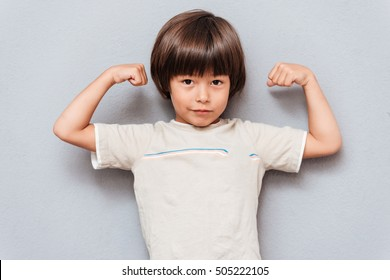 Cute little boy standing and showing biceps over gray background