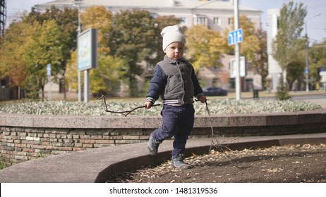 Cute little boy with sticks standing on urban flowerbed in autumn. With no flowers on the flowerbed.