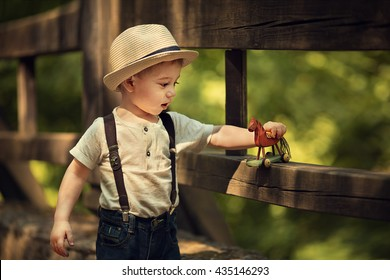Cute little boy in straw hat playing with wooden horse on the wooden bridge. Image with selective focus and toning
