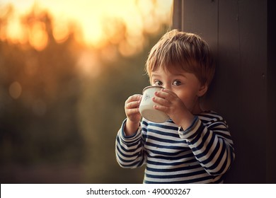 Cute little boy in striped vest is drinking from the iron cup with flower during the sunset in the country. Image with selective focus and toning