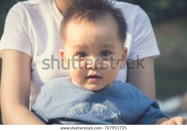cute little boy stting on mother leg looking at camera with big brown eyes