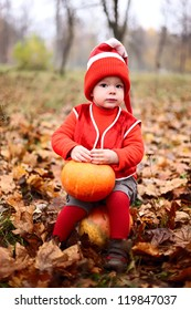 cute little boy in a suit with a pumpkin gnome in autumn park