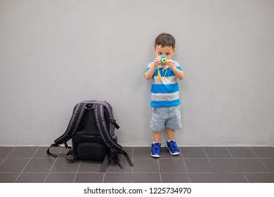 Cute little boy with suitcase and toy camera at airport.  Travel concept. Copy space. Background.
