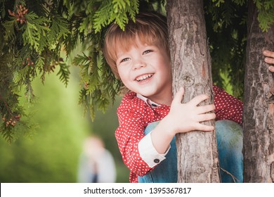 Cute little boy at summer day playing and smiling, closeup portrait near green tree