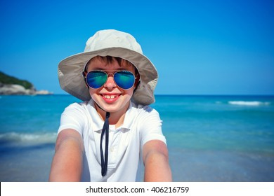 Cute little boy in sunglasses making selfie at tropical beach on exotic island during summer vacation