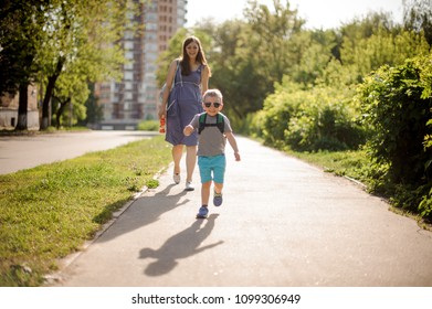 Cute little boy in sunglasses walking down the street with his mother on sunny summer day