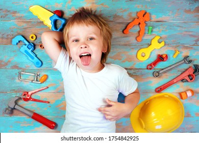 Cute little boy surrounded by toy tools top view. Happy boy playing with a  toy tools set. Early childhood education concept