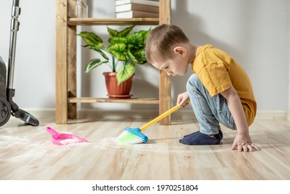 A cute little boy is sweeping the trash from the floor with a broom to a dustpan. Child helps the parents in cleaning the house