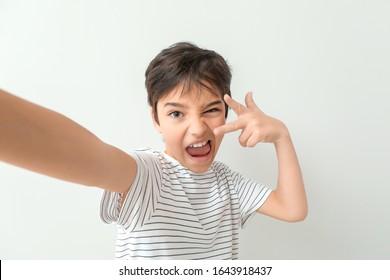 Cute little boy taking selfie on light background