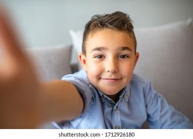 Cute little boy taking selfie on light background. Happy little boy with healthy teeth taking selfie. Photo of boy takes selfie with smart phone indoors. Boy takes selfie