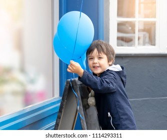 Cute little boy with teddy bear holding blue balloon with smiling face, Happy child playing with air balloons outdoor,