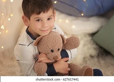 Cute little boy with teddy bear at home