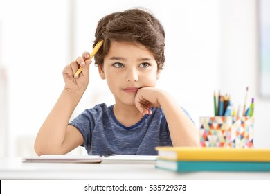 Cute little boy thinking about something, on blurred background