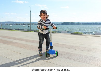 Cute little boy with three-wheeled scooter