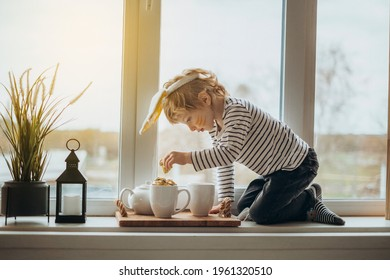 Cute little boy toddler with bunny ears headband sitting on big cozy and pretty decorated windowsill, l oking at window, enjoying view outdoor, feeling comfort with reliable window systems - Shutterstock ID 1961320510