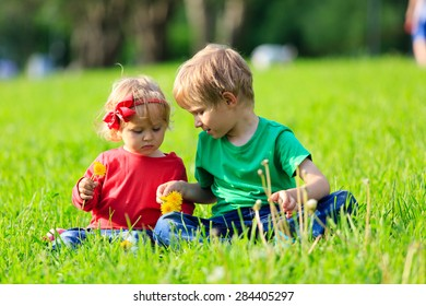 Cute little boy and toddler girl playing with dandelions on green grass