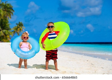 cute little boy and toddler girl play on beach