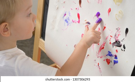 Cute little boy (toddler, two years old) is painting. Washable finger paints for Babies Kids. Art, creative, early childhood education to children concept, kindergarten, pre-primary, nursery school.