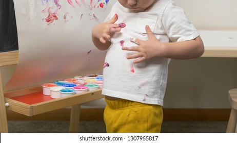 Cute little boy (toddler, two years old) is painting on tee. Washable finger paints for Babies Kids, art, creative. Dirty cloth (t-shirt), washing laundry concept