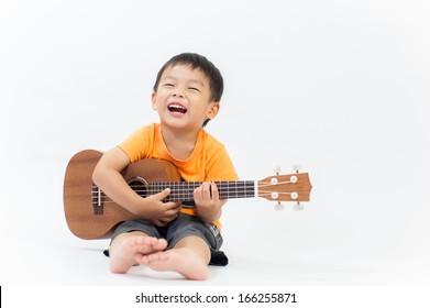 Cute little boy with ukulele guitar