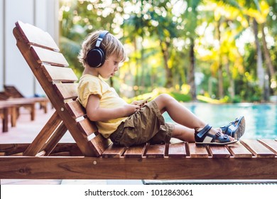 A cute little boy is using a smartphone and headphones lying on a deckchair by the pool. primary education, friendship, childhood, technology and people concept.