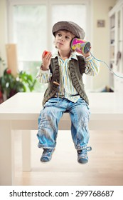 Cute little boy in vintage outfit sitting on a table and eating strawberry while playing with a tin can telephone