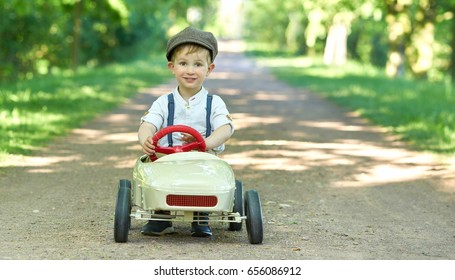 Cute Little Boy With Vintage Pedal Car Outside In Nature Retro Style