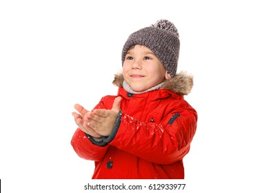 Cute little boy in warm clothes playing with snow on white background
