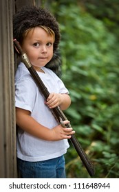 cute little boy wearing a coonskin cap and holding a toy rifle