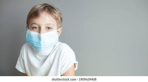 Cute little boy wearing health mask, looking up, isolated over grey background
