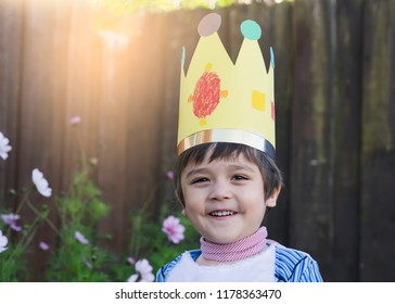 Cute little boy with wearing king crown making by paper for his home work,Happy boy wearing mismatched costume for school party, Creative and Development idea for early years student.