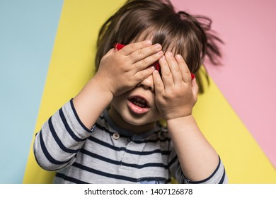 Cute little boy wearing striped top covers his eyes with hands, playing peek a boo, hide and seek, or while waiting a fun birthday surprise, on a cheerful, colorful studio backdrop. Childhood games.