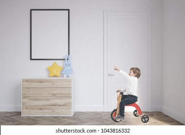 Cute little boy in a white shirt and dark blue jeans is riding a tricycle and showing with his finger. A baby boy room background with a poster above a set of drawers